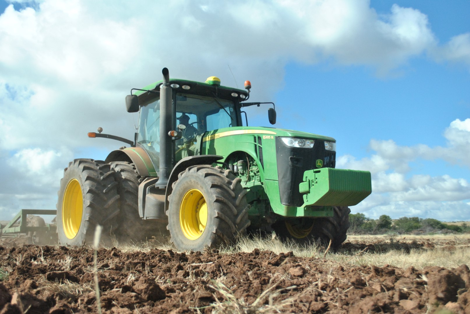 Green tractor ploughing a field